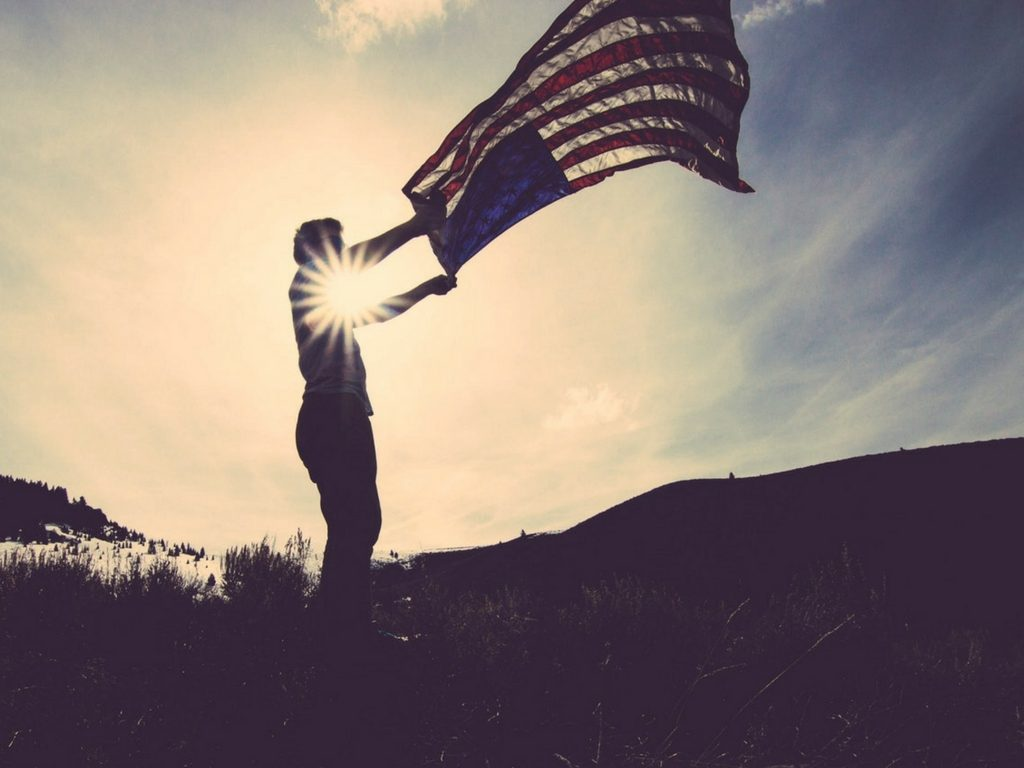 Man shaking out an American flag to celebrate Veterans with the sun and sky behind him while he's in shadow