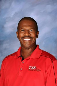 Photo of a man with dark hair, wearing a red shirt on a blue background he's a franchise owner named Gerald Jordan.