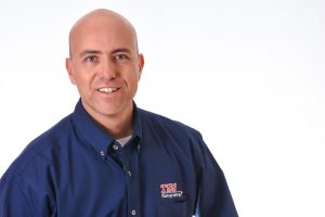 man with a clean shaven head in a blue button-down shirt on a white background, he is a franchise owner named Guillermo Palos.