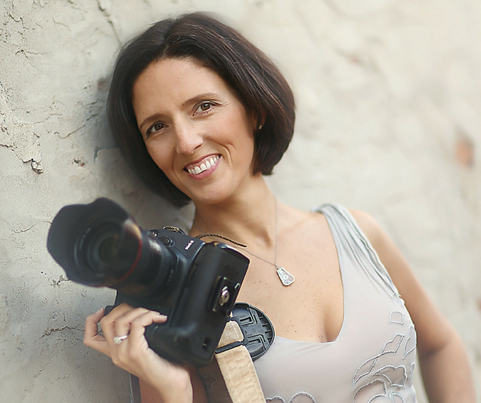 Brunette leaning against a tan wall holding a digital camera smiling wearing a v-neck tank top