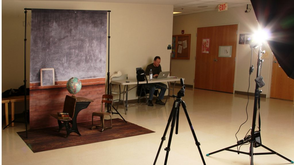 Set of a school casual photo shoot in the hallway with a prop blackboard and a globe on a desk with a camera and a professional flash