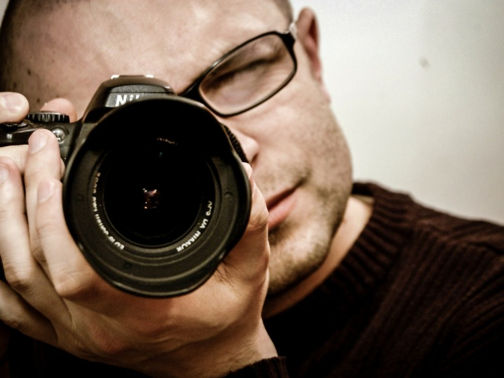 Male photographer in black sweater with black framed glasses shooting a camera up close