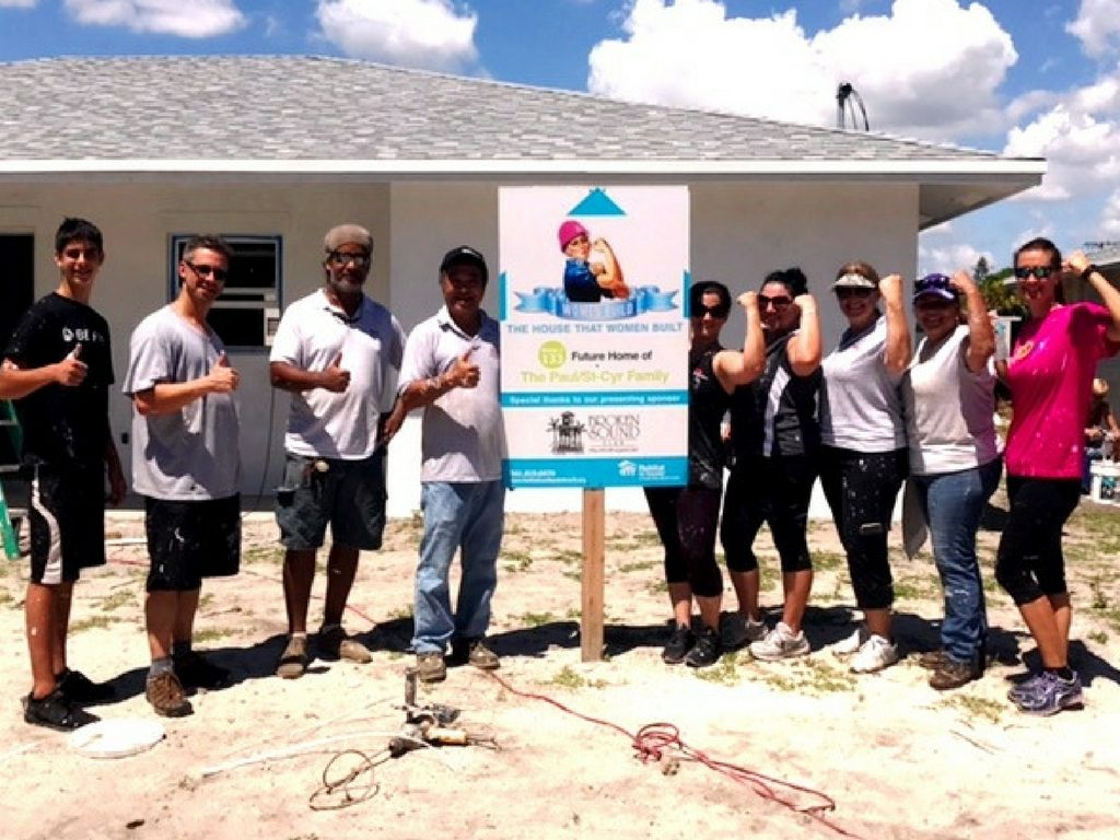Group of nine people posing in front of a Habitat for Humanity House they volunteered at
