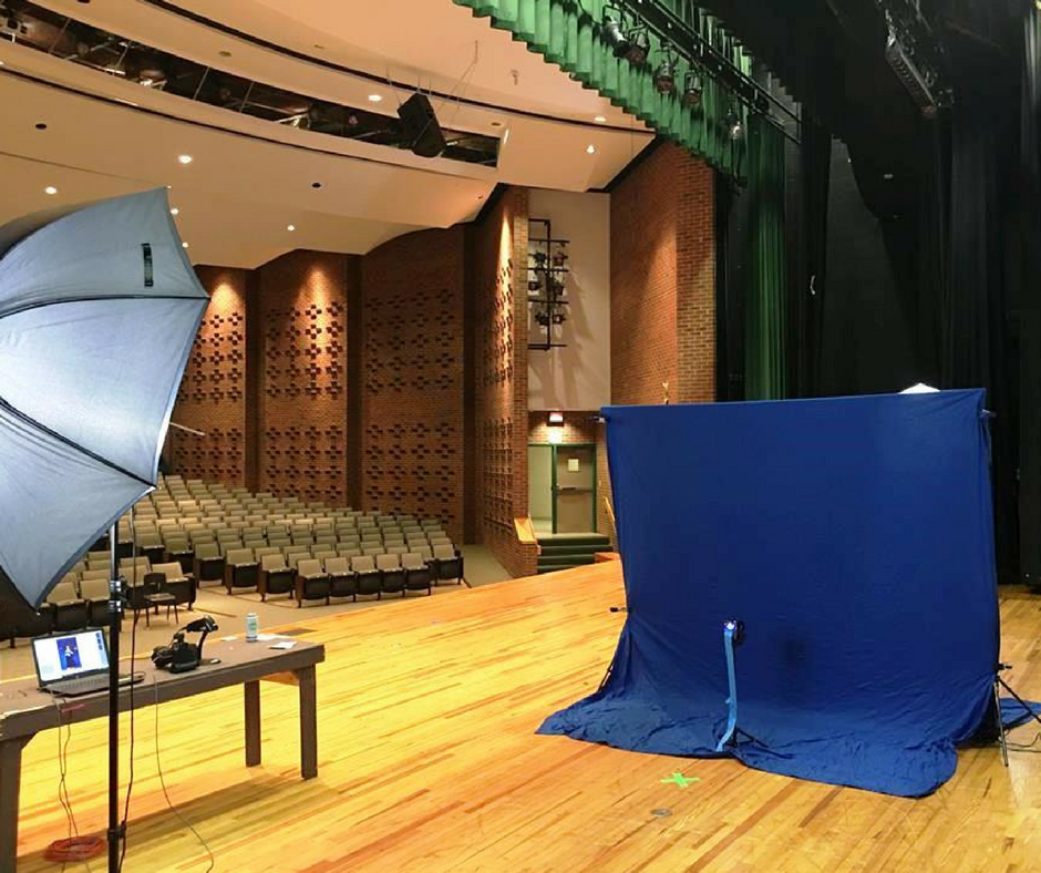 Blue backdrop and equipment bag set up in a theater for a photography shoot by TSS Photography