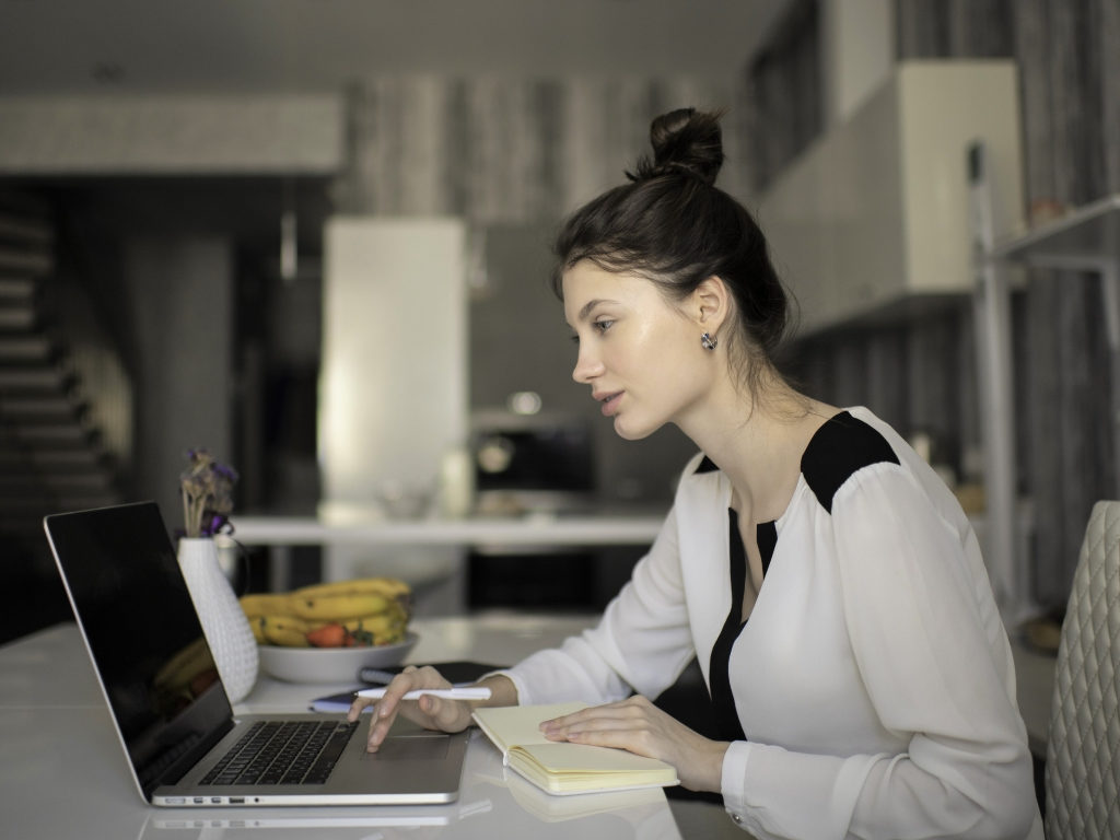 A woman works in her at home office in front of a laptop with a kitchen in the background
